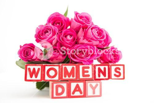 Bouquet of pink roses next to wooden blocks spelling womens day