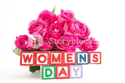 Bunch of pink roses next to wooden blocks spelling womens day