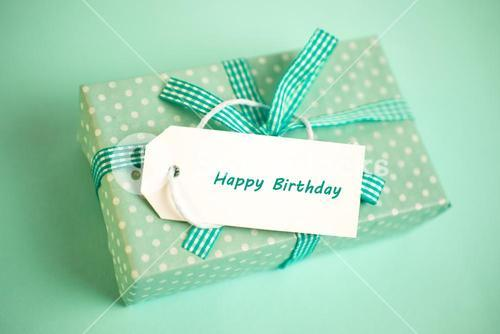Pretty green gift with a happy birthday card on a green background