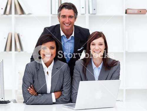 Enthusiastic businesswomen and their colleague working at a laptop