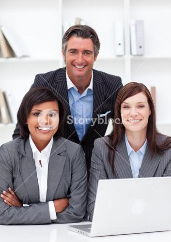 Smiling business partners using a laptop