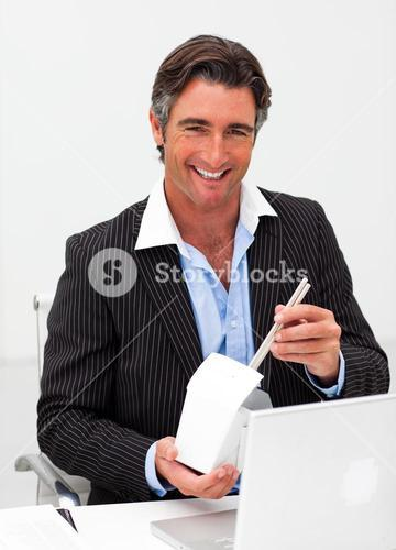 Portrait of a smiling businessman eating chines food