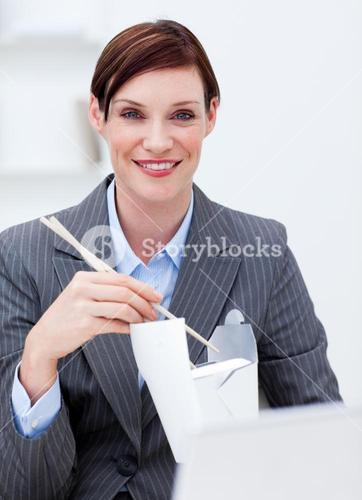 Businesswoman eating chinese food at work