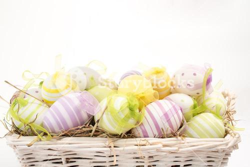 Many colourful easter eggs in basket