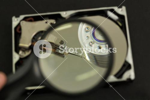 Hand holding magnifying glass over disk drive