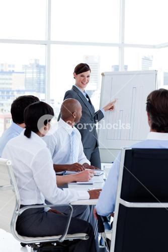 Smiling business woman doing a presentation to her colleagues