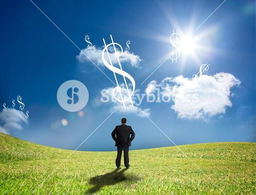 Businessman looking up at dollar signs in the sky