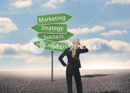Businesswoman looking at signposts with marketing terms