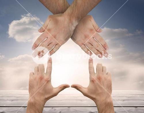 Hands crossed representing a house with blue sky