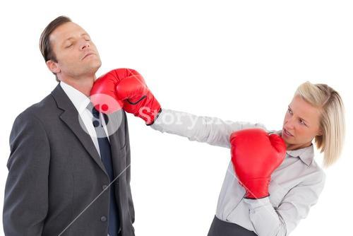 Businesswoman hitting colleague with boxing gloves