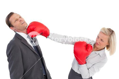 Businesswoman hitting colleague with her boxing gloves