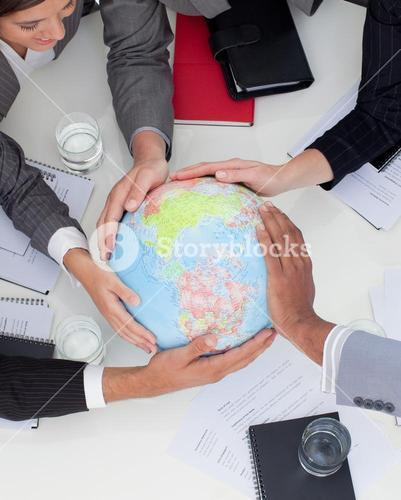 Close up of business people holding a terrestrial globe