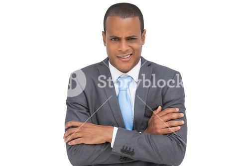 Doubtful young businessman with arms crossed