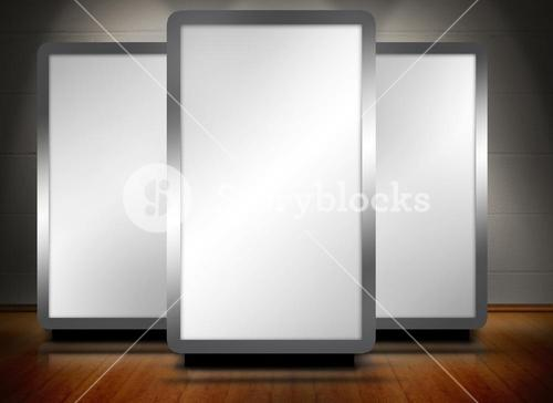 Three blank screens standing on wooden floor