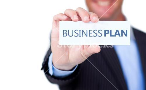 Businessman holding a label with business plan written on it