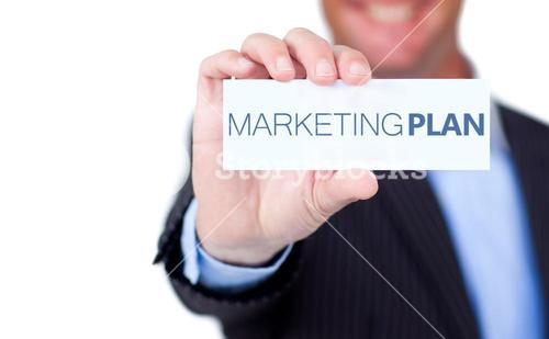 Businessman holding a label with marketing plan written on it