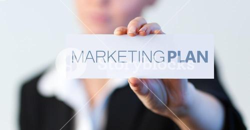 Businesswoman holding a label with marketing plan written on it