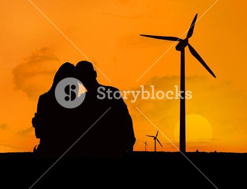 Couple embracing in front of a sunset