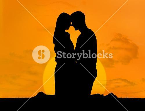 Silhouette of couple embracing under a sunset