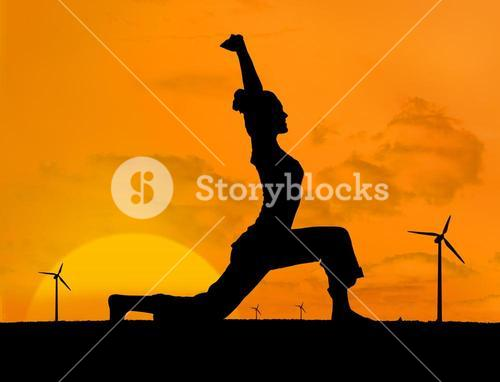 Silhouette of woman doing yoga with wind turbines