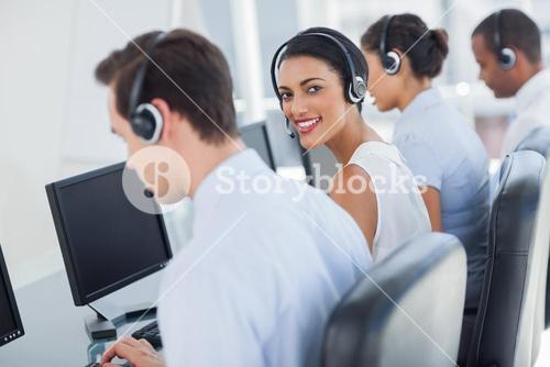 Smiling call centre employee looking over shoulder