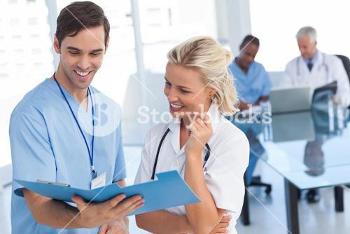 Two smiling doctors talking about a blue file