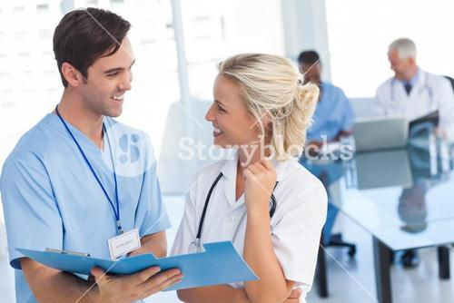 Two young doctors talking about a blue file