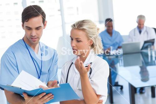 Young doctors talking about a blue file