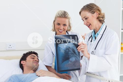 Two women doctors showing xray to a patient