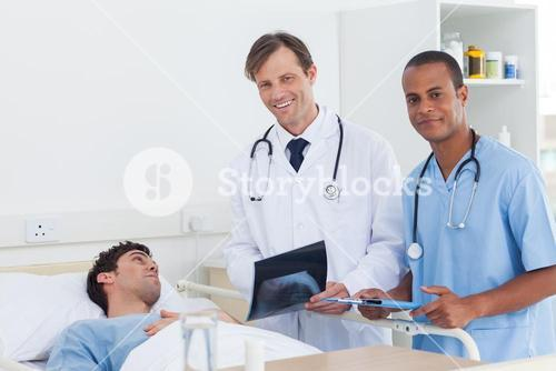 Doctors with radiography standing next to a patient