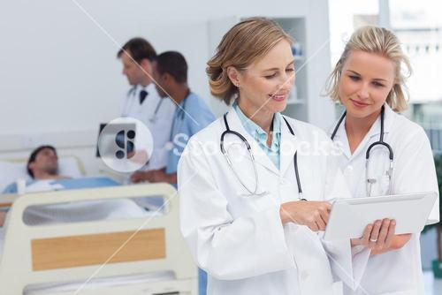 Two women doctors looking at tablet