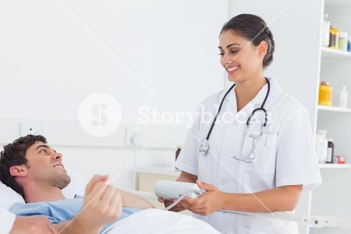 Attractive nurse measuring the blood pressure of a patient