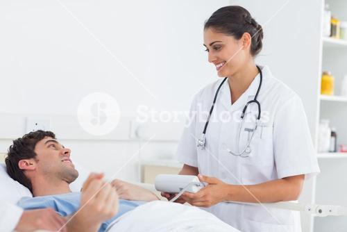 Attractive doctor taking the blood pressure of a patient