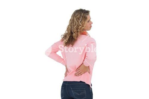 Woman having a back ache and holding her back