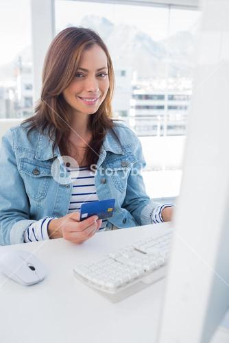 Smiling woman purchasing online with her credit card