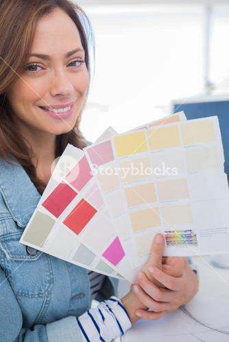 Cheerful interior designer holding up colour samples
