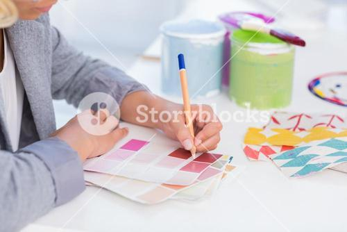 Pretty interior designer drawing on colour samples