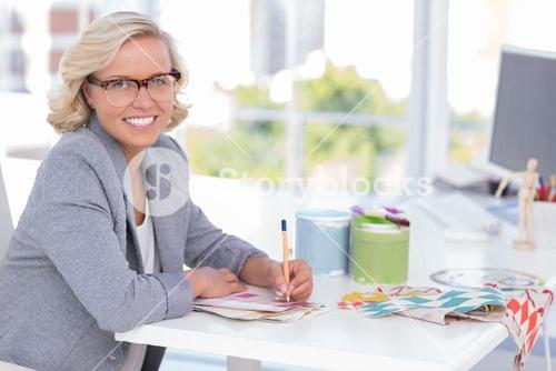 Cheerful interior designer working on colour charts