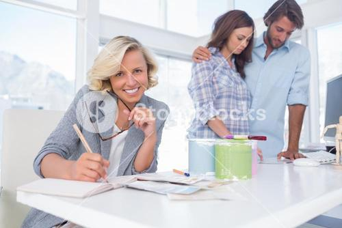 Smiling designer with a couple in her office