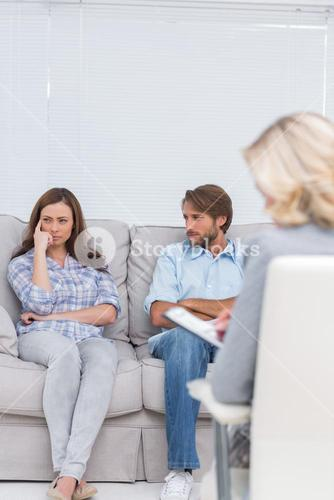 Troubled couple sit with arms folded