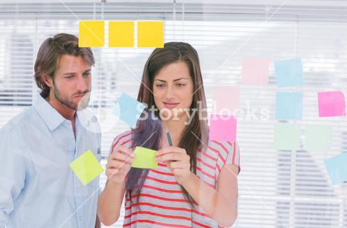 Colleagues pasting sticky note