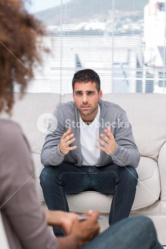 Upset man speaking to a therapist