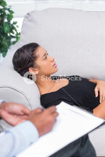 Woman lying down a sofa during a psychotherapy