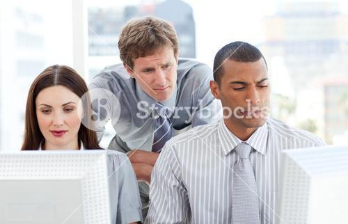 Serious businesspeople working at computers with their manager