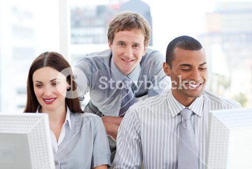Two businesspeople working at computers with their manager