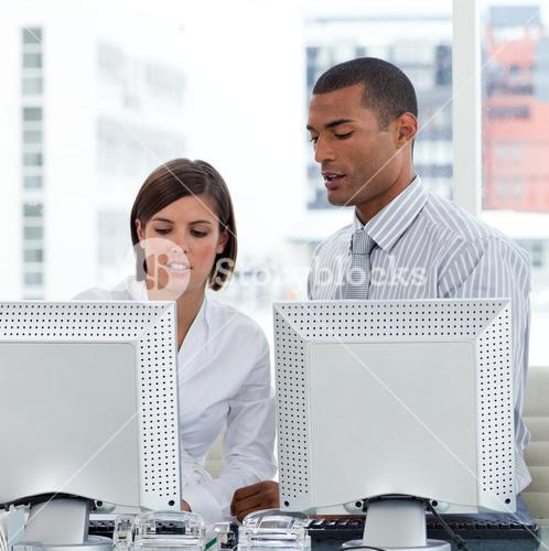 Two business people helping each other with their computers