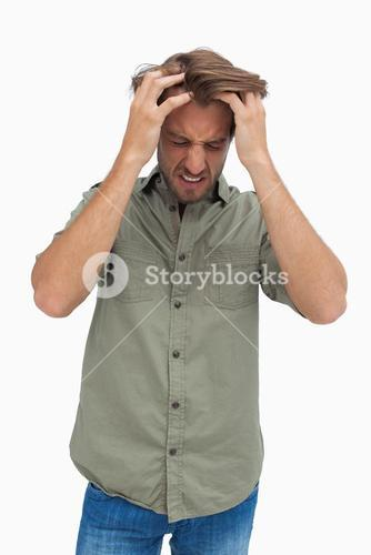 Frustrated man pulling his hair and looking down