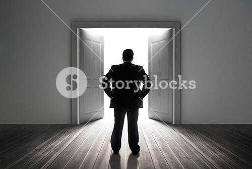 Businessman looking at door showing bright light