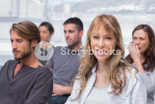 Patients listening in group therapy with one woman smiling
