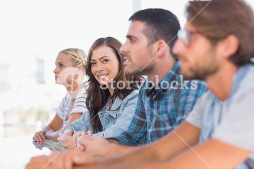 Creative team sitting in a line with one woman smiling